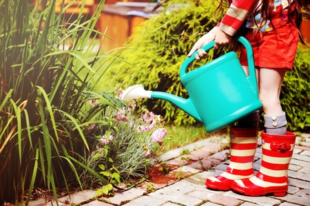 Little girl in a garden with green watering pot photo