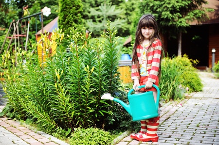 Little girl in a garden with green watering pot Stock Photo - 14529163