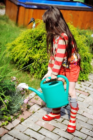 rubber plant: Little girl in a garden with green watering pot Stock Photo