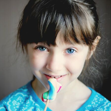 Close-up portrait of cute brunette little girl with candy photo