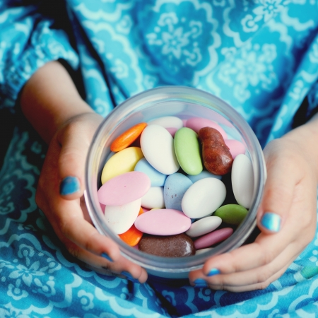 Box with colorful candies in the hands of little girl, focus on candies photo