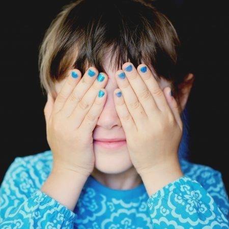 hand covering eye: Little girl with her hands covering her eyes, see no evil