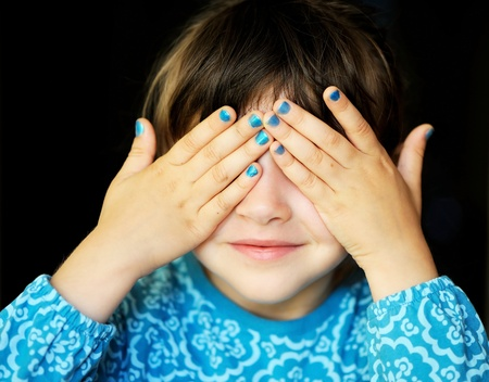 Little girl with her hands covering her eyes, see no evil photo