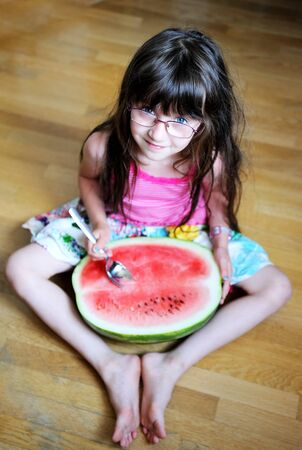 Cute little girl eating watermelon with a spoon on the floor photo