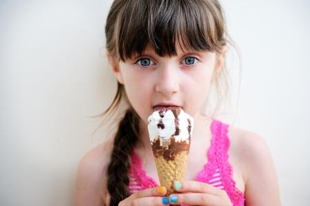 Cute brunette little girl eating ice cream Stock Photo
