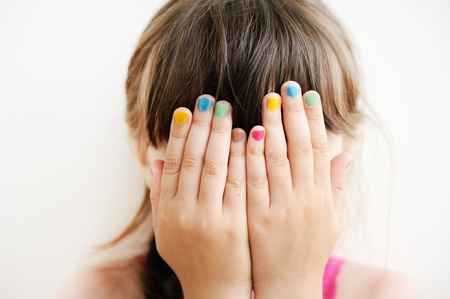 eyes hidden: Little girl with her hands covering her eyes, see no evil