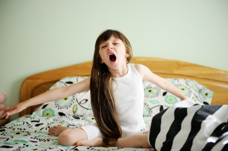 Portrait of little girl sitting in bed in early morning Stock Photo