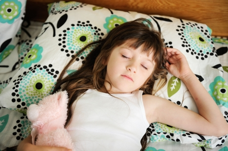 nap: Portrait of little girl sleeping in bed in early morning