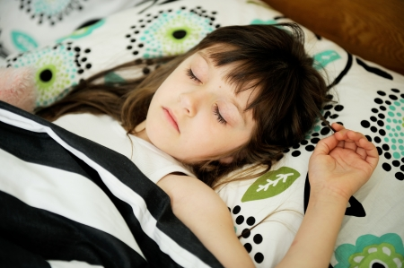 Portrait of little girl sleeping in bed in early morning photo