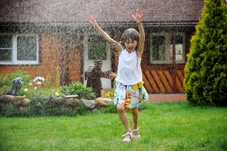 kids playing water: Little girl refreshing herself under splashes of water in a garden, slight motion blur Stock Photo