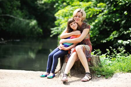 single parents: Outdoor portrait of a young mother embracing her little daughter in the park Stock Photo