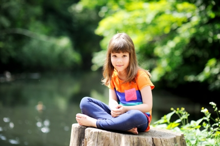 Outdoor portrait of little girl sitting on stump in lotuis pose photo