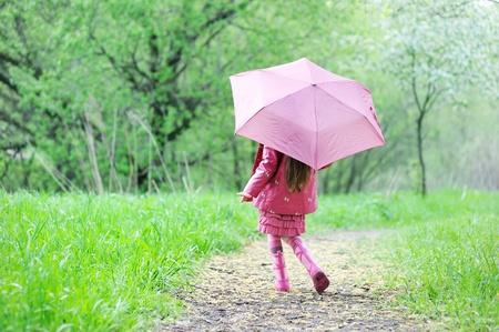 botas de lluvia: Muchacha del cabrito en un impermeable caminar al aire libre con el paraguas rosado Foto de archivo