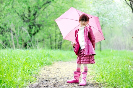 Kid girl in a raincoat posing outdoors with pink umbrella photo