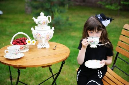 Portrait der eleganten Kind Mädchen in einem schwarzen Kleid mit einem Tee-Party im Freien