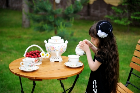 Portrait of elegant child girl in a black dress having a tea party outdoors