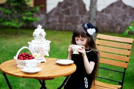kids dress: Portrait of elegant child girl in a black dress having a tea party outdoors