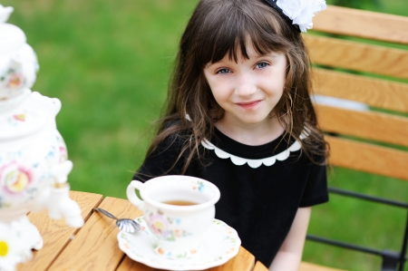 tea party: Portrait of elegant child girl in a black dress having a tea party outdoors