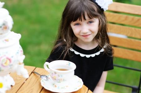 elegant party: Portrait of elegant child girl in a black dress having a tea party outdoors