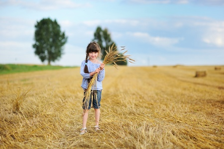haystack: Little girl on a field holding bunch of wheat spikelet