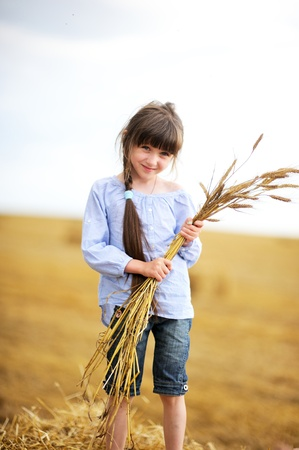 Little girl on a field holding bunch of wheat ears photo