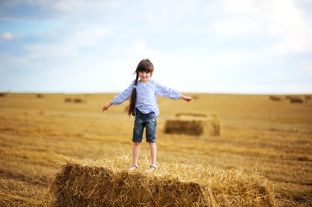 Little girl standing on a top of big haystack in the middle of the field photo
