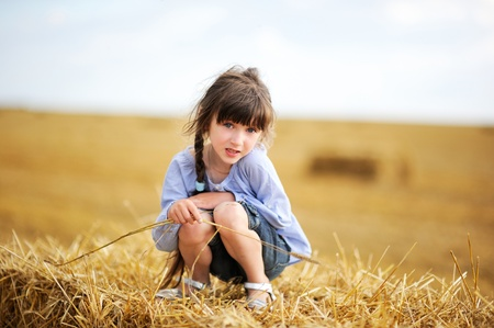 Little girl sitting on a top of haystack in the middle of the field photo