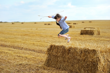 haystack: Little girl jumping from a top of haystack in the middle of the field