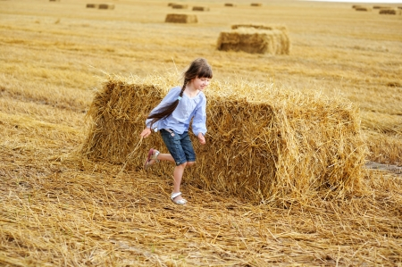Little girl running around a haystack on a field photo