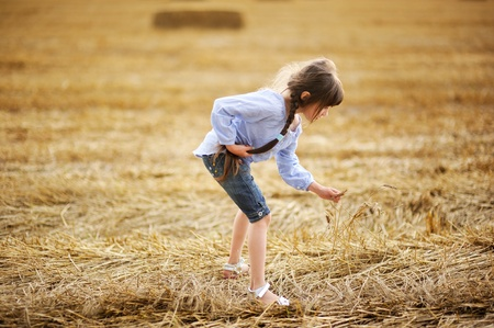 Little girl picking up dry straws on a field photo