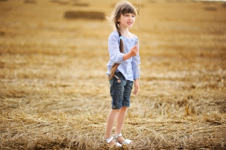 Little girl on a field holding wheat spikelet photo