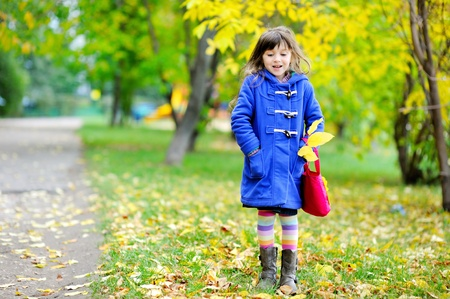 Funky little girl in blue coat posing on the street with pink bag