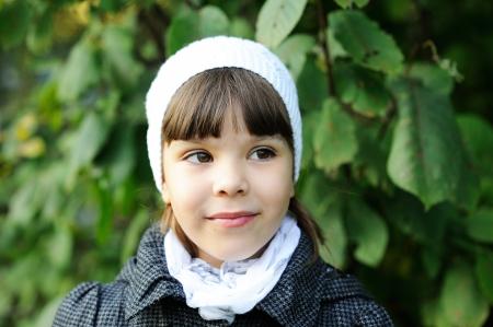 brown skin: Autumn outdoor portrait of little girl wearing white hat