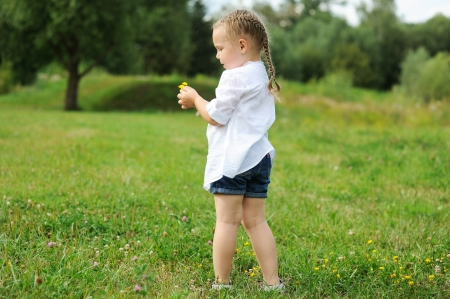 alone person: Little child girl gathering flowers on a meadow