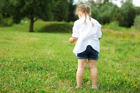 baby hairstyle: Little child girl gathering flowers on a meadow