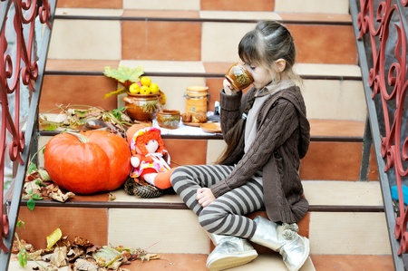 Little girl drinking tea outdoors on stairs photo