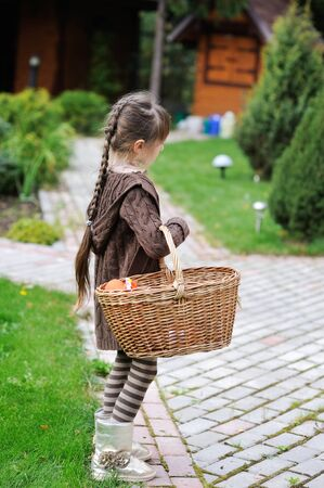 Little girl posing outdoors with garden basket photo