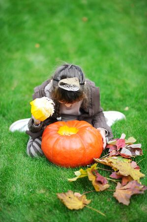 Little girl sitting on grass and looking inside big orange pumpkin photo