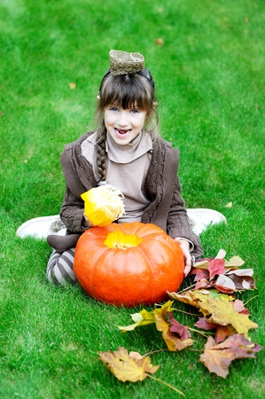 Little girl lying on a grass with big orange pumpkin photo