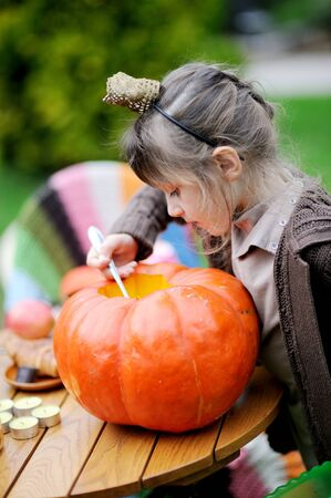 Little girl looking inside big orange pumpkin photo