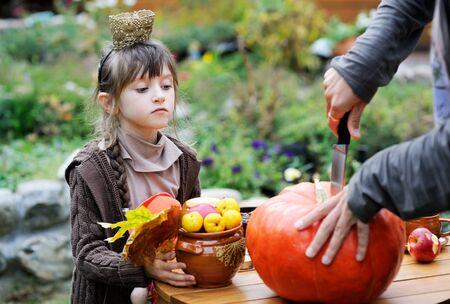 large pumpkin: Little girl watching the carving of big orange pumpkin