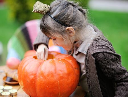 Little girl looking inside big orange pumpkin Stock Photo - 15529768