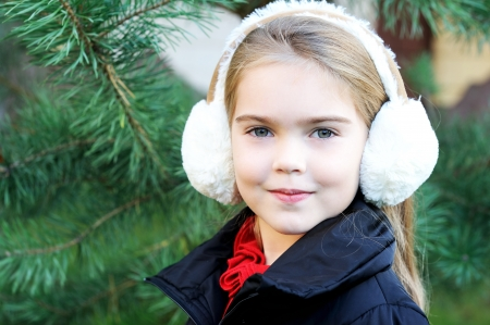 Outdoor portrait of little girl wearing white earmuffs photo