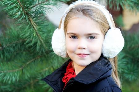 Outdoor portrait of little girl wearing white earmuffs Stock Photo