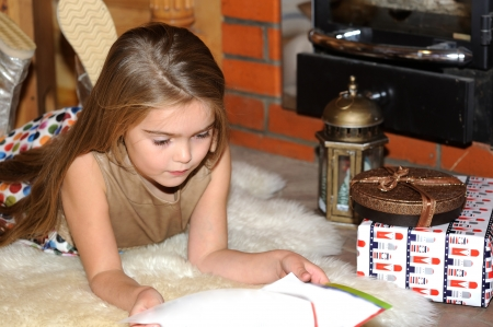 Child girl is reading a book in front of fireplace Stock Photo - 16494791