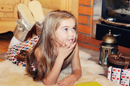 Child girl is reading a book in front of fireplace Stock Photo - 16494822