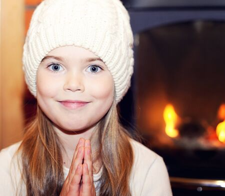 Portrait of child girl in white hat posing by the fireplace photo