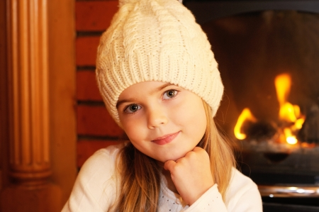 Portrait of child girl in white hat posing by the fireplace Stock Photo - 16494798