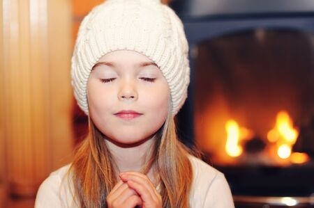 Portrait of child girl in white hat praying by the fireplace with closed eyes photo