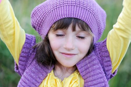 one eye closed: Close-up portrait of little girl in violet hat with closed eyes